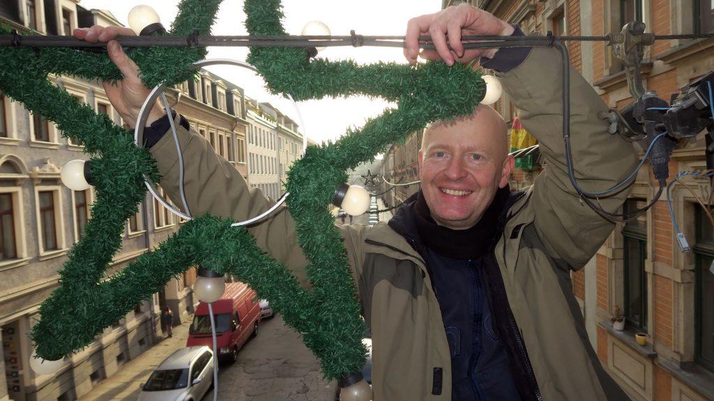 Der Projektleiter des Gewerbe- und Kulturvereins hängt Weihnachtssterne auf.